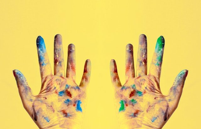two hands stained with paint on yellow background