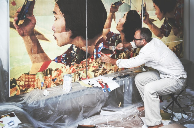a man in white painting an abstract piece of a lady